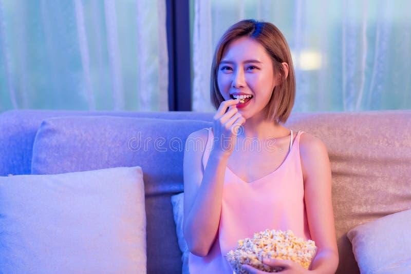 Kvinnaklockafilm med popcorn royaltyfri bild