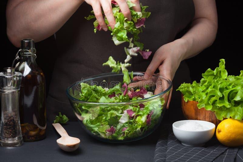Kvinnakock i salladen för kökmatlagninggrönsak äta som är sunt begreppet bantar En sund livsföring Kock hemma Till arkivfoton