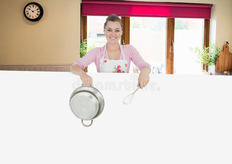 kvinnakock med kastrullen och affischen i köket royaltyfria bilder