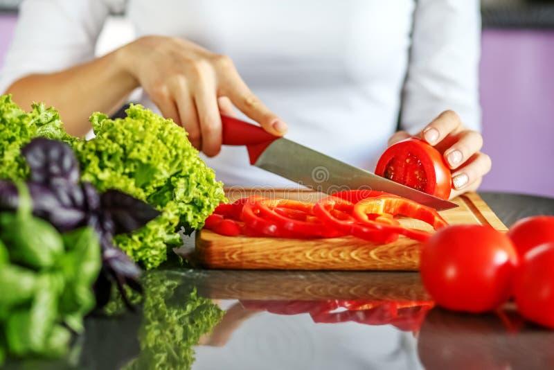 Kvinnakock som skivar grönsaker i köket Begreppet är heaen royaltyfri foto