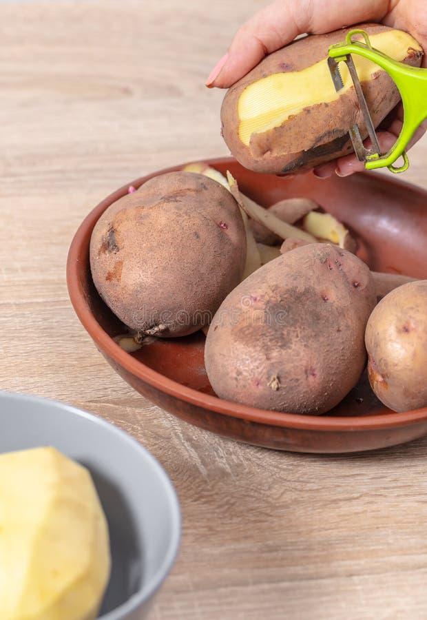 kvinnakocken gör ren potatisar arkivbild