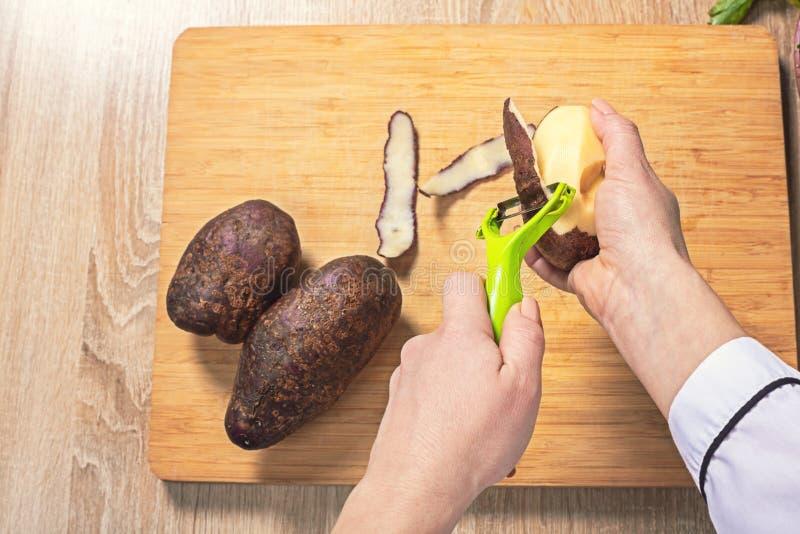 kvinnakocken g?r ren potatisar fotografering för bildbyråer