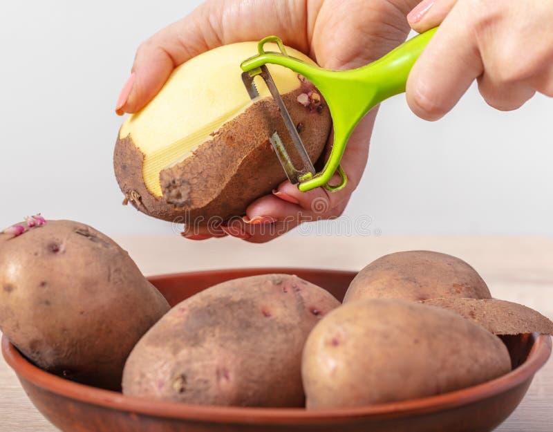 kvinnakocken g?r ren potatisar arkivfoto