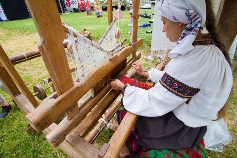 Kvinnakonstnär i ukrainska traditionella kläderarbeten på den forntida vävstolen som väver matta arkivfoto