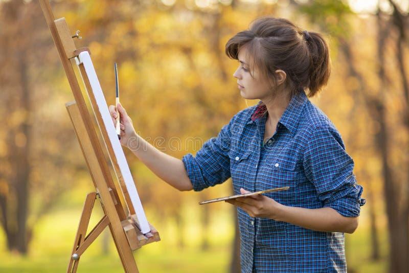 Kvinnakonstnär som drar en bild på en staffli i natur, en flicka med en borste och en palett, ett begrepp av kreativitet och en h royaltyfria bilder