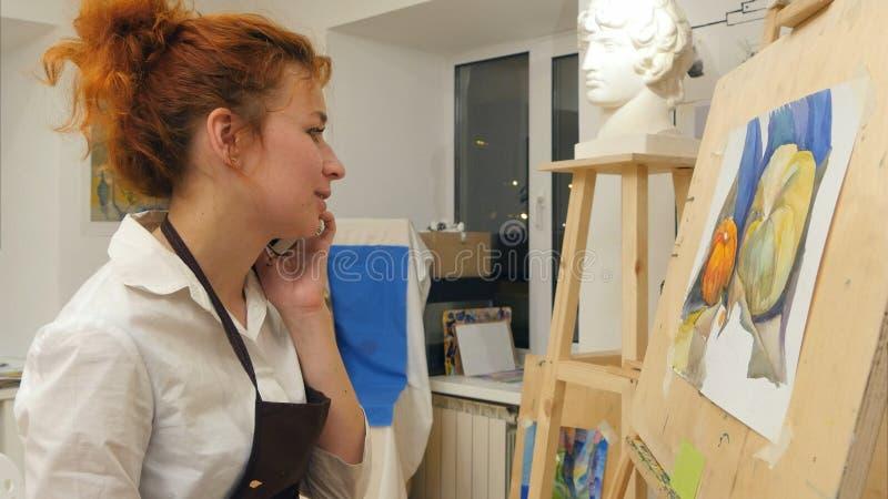 Kvinnakonstnär som målar en bild, medan tala på telefonen arkivfoton
