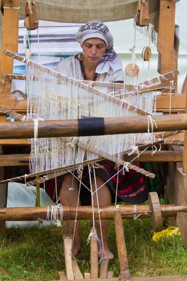 Kvinnakonstnären arbetar på den forntida vävstolen som väver matta royaltyfri bild