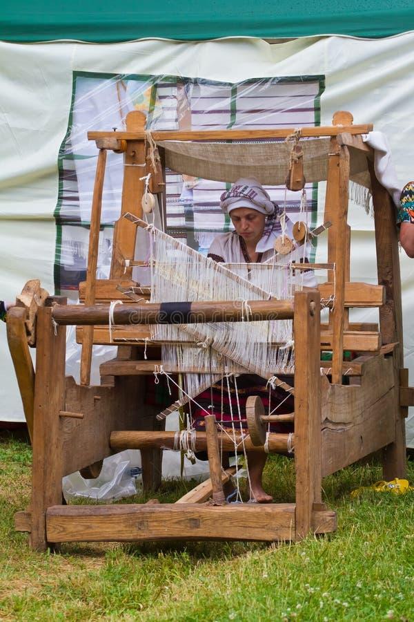 Kvinnakonstnären arbetar på den forntida vävstolen som väver matta royaltyfri foto