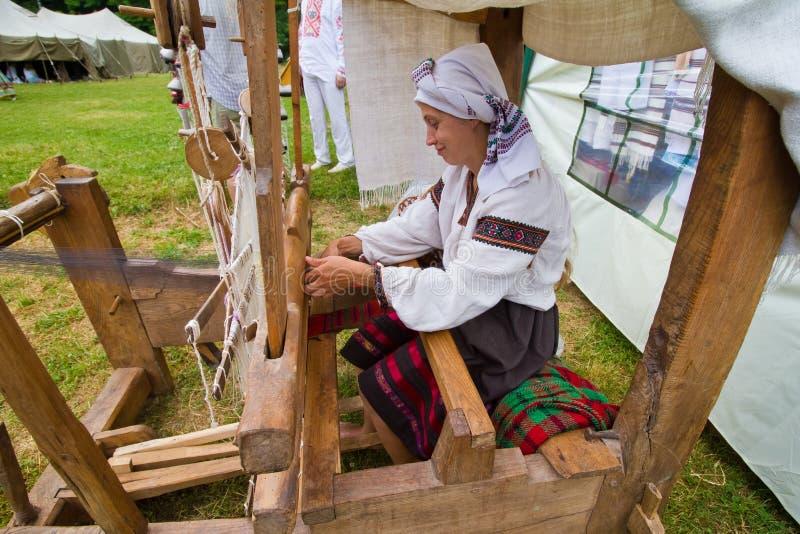 Kvinnakonstnären arbetar på den historiska vävstolen som väver tyg på Live Fire Midsummer Pagan Ethnofestival arkivbilder
