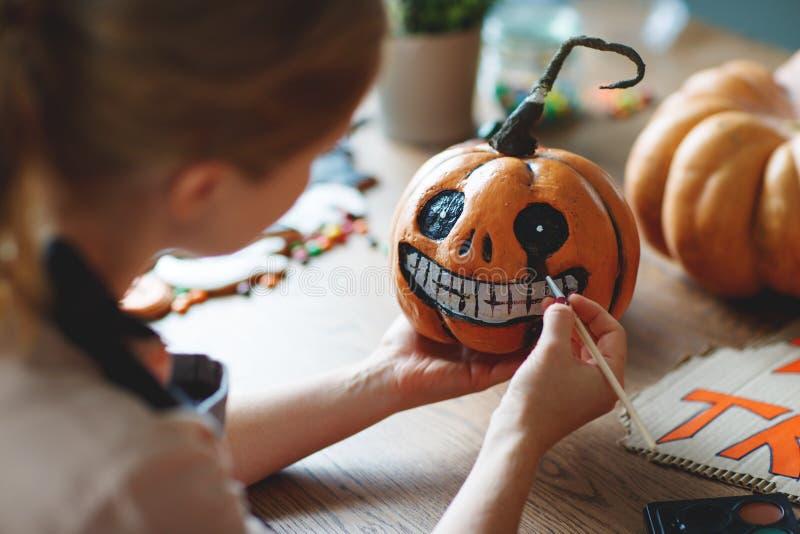 Kvinnakonstnären förbereder sig för halloween och målar pumpor royaltyfria bilder