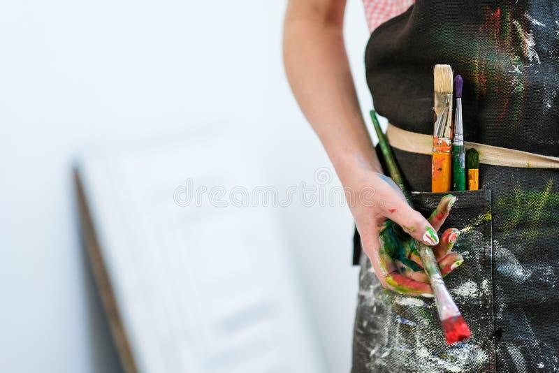 Kvinnakonstnärs hand med en borste och en röd målarfärg Svart förkläde, vit bakgrund royaltyfri foto
