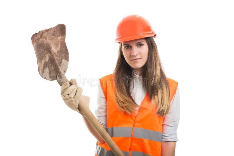 Kvinnakonstruktörarbetare som rymmer en skyffel arkivbild