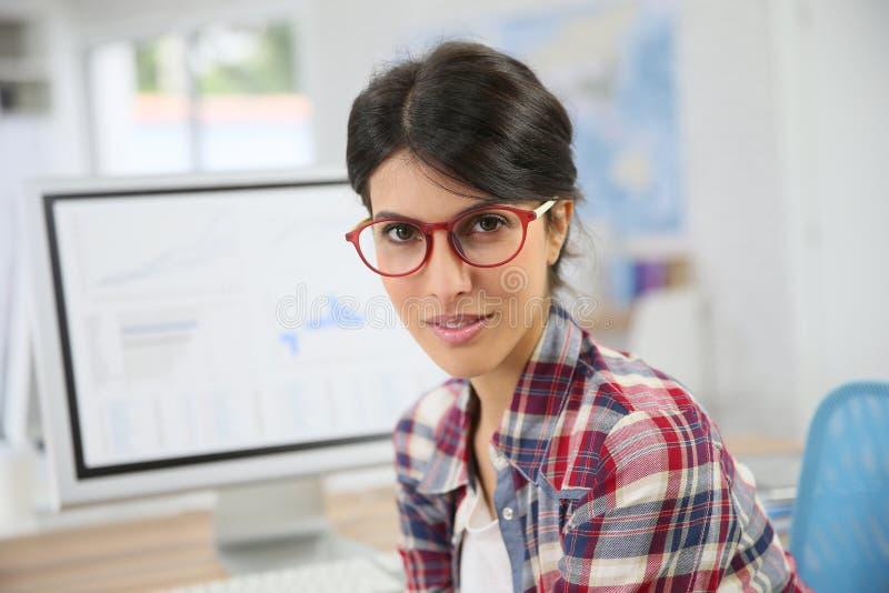 Kvinnakontorsarbetare med exponeringsglas fotografering för bildbyråer