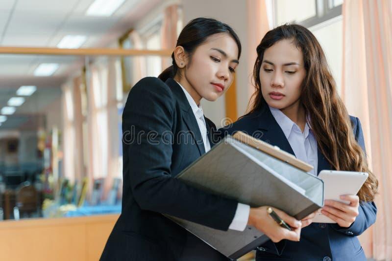 Kvinnakontorsarbetare som tillsammans arbetar arkivbilder