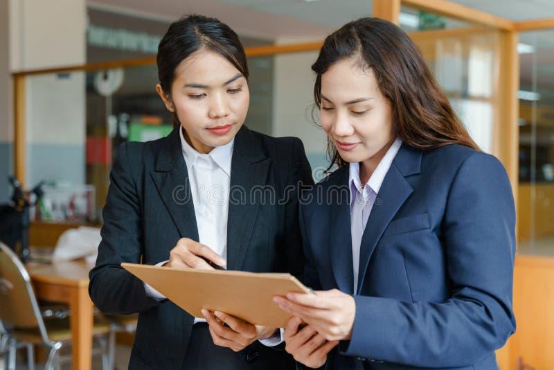 Kvinnakontorsarbetare som tillsammans arbetar royaltyfri foto