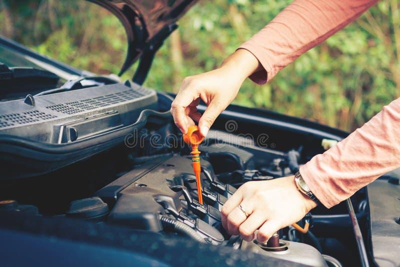 Kvinnakontroll motoroljan av bilen fotografering för bildbyråer