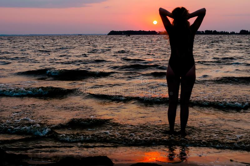 Kvinnakontur i baddräkt med lyftta armar som ser förbluffa soluppgång nära havet royaltyfri foto