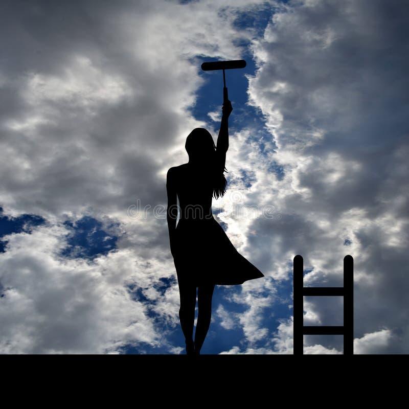 Kvinnakontur med stegen på taket som målar himlen arkivfoto