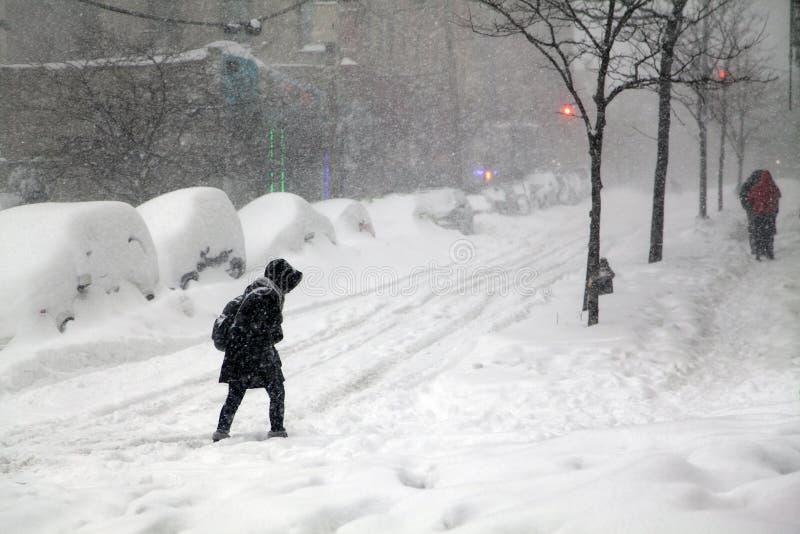 Kvinnakorsning gata under snöhäftiga snöstormen Jonas i Bronxen arkivfoto