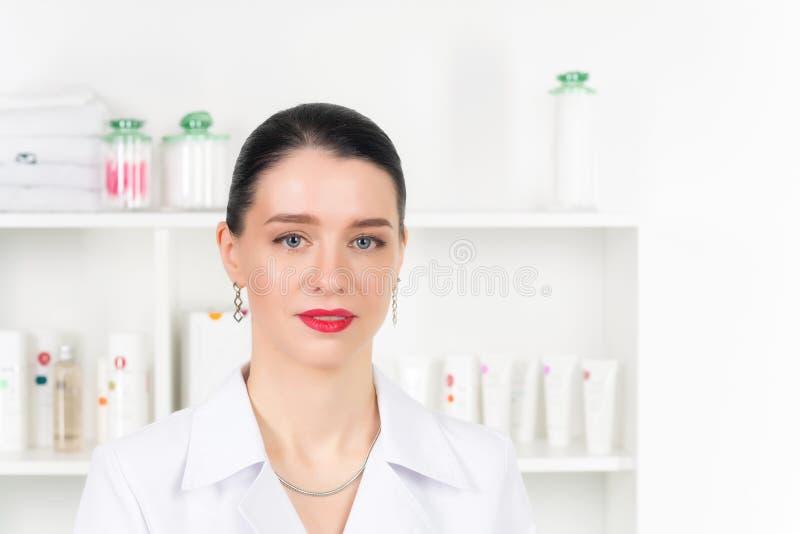 Kvinnakosmetologdoktor på arbete i brunnsortmitt Stående av ung kvinnlig yrkesmässig cosmetologistFemale anställd in royaltyfria bilder
