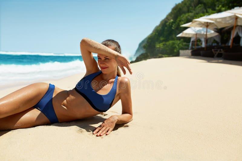 Kvinnakropp i sommar Flicka i bikini som garvar på stranden arkivbild