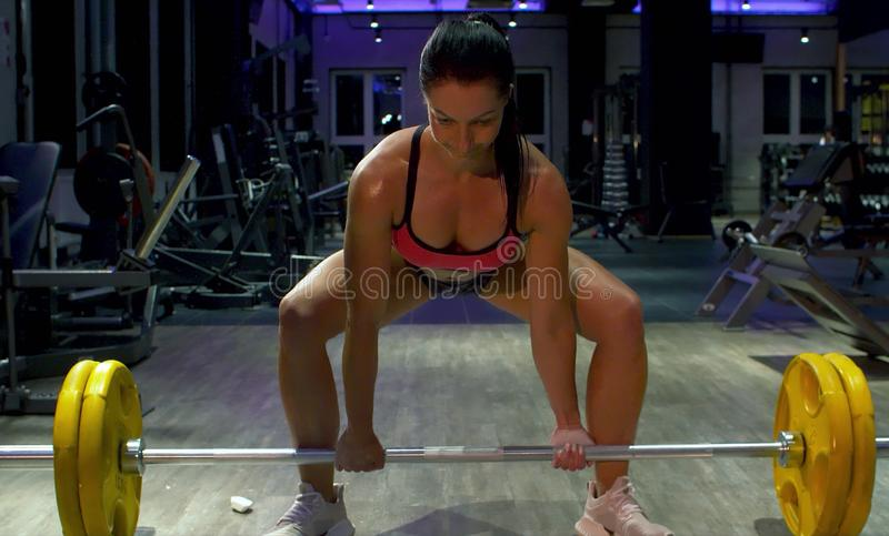 Kvinnakroppsbyggarelyftande skivstång Idrottsman nen i idrottshallen royaltyfri fotografi