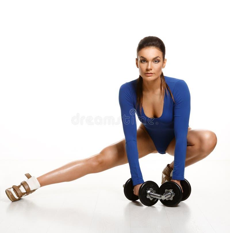 Kvinnakroppsbyggaren i blå bodysuit, utför en övning med du royaltyfri bild
