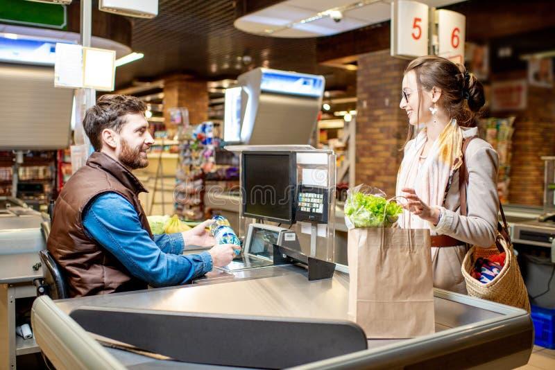 Kvinnakund med kassörskan i supermarket royaltyfri fotografi