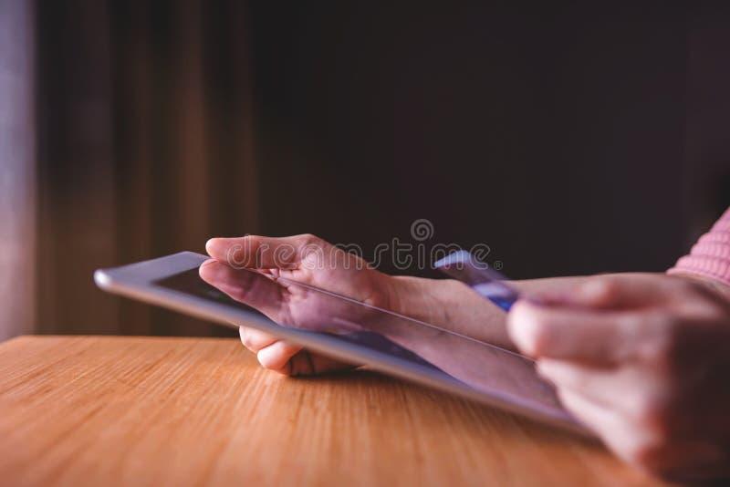 Kvinnakund som använder kreditkorten och minnestavlan till att shoppa direktanslutet arkivbilder