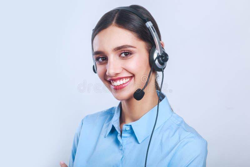Kvinnakundtjänstarbetare, appellmitt som ler operatören med telefonhörlurar med mikrofon fotografering för bildbyråer