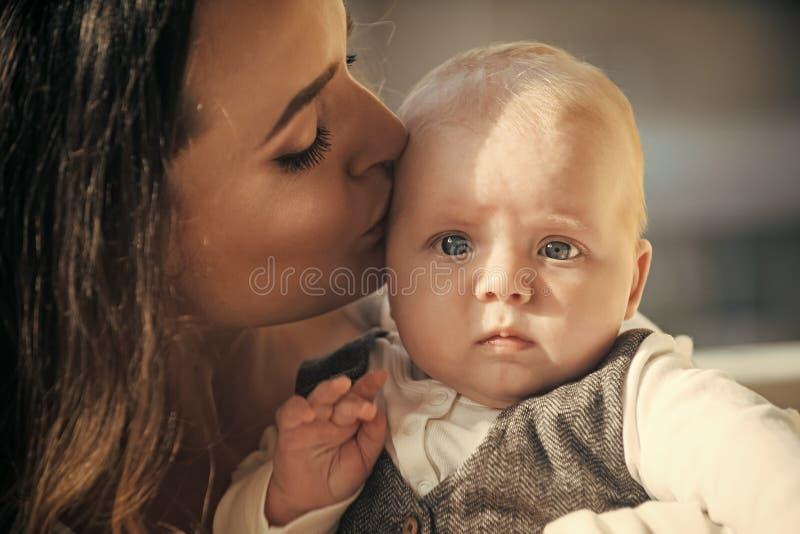 Kvinnakyssen behandla som ett barn pojken med blåa ögon på gullig framsida royaltyfri bild