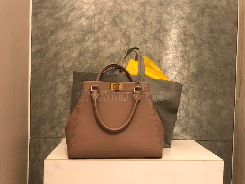 Kvinnaläderhandväska med shoppingpåsar arkivfoto