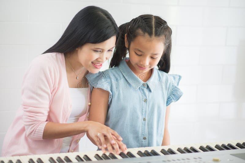 Kvinnaläraren undervisar pianot en flicka arkivbild