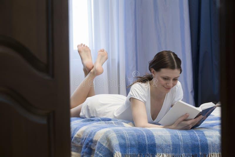 Kvinnaläsebok i säng arkivfoton