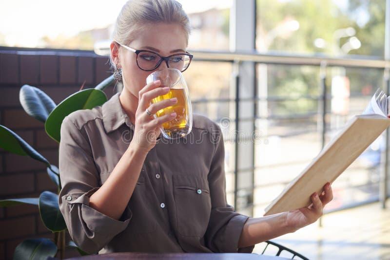 Kvinnaläsebok, medan dricka örtte på kafét royaltyfri foto