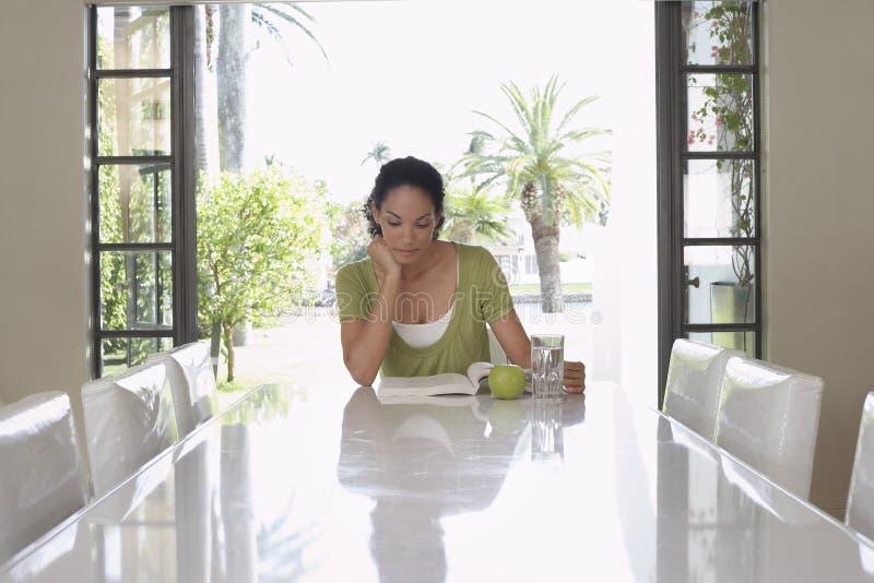 Kvinnaläsebok på att äta middag tabellen royaltyfri bild