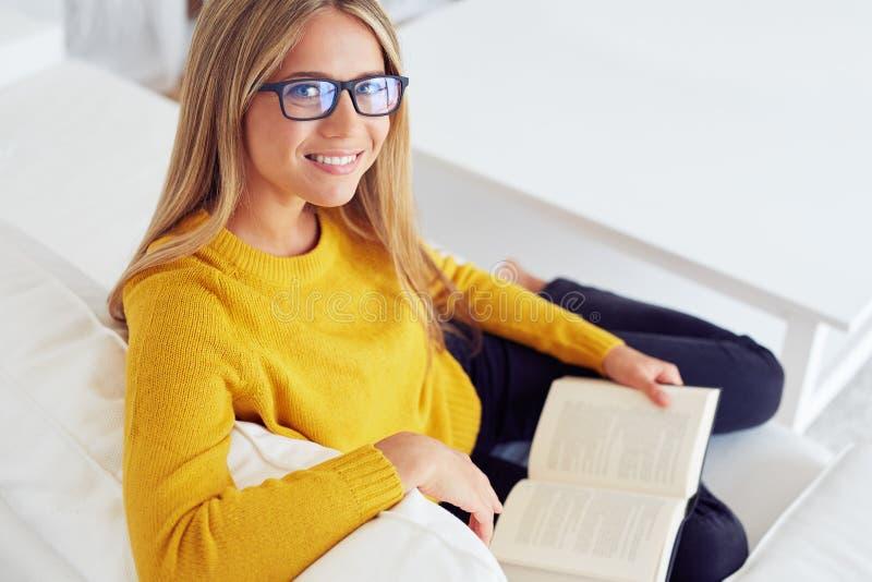 Kvinnaläsebok på soffan hemma arkivfoton