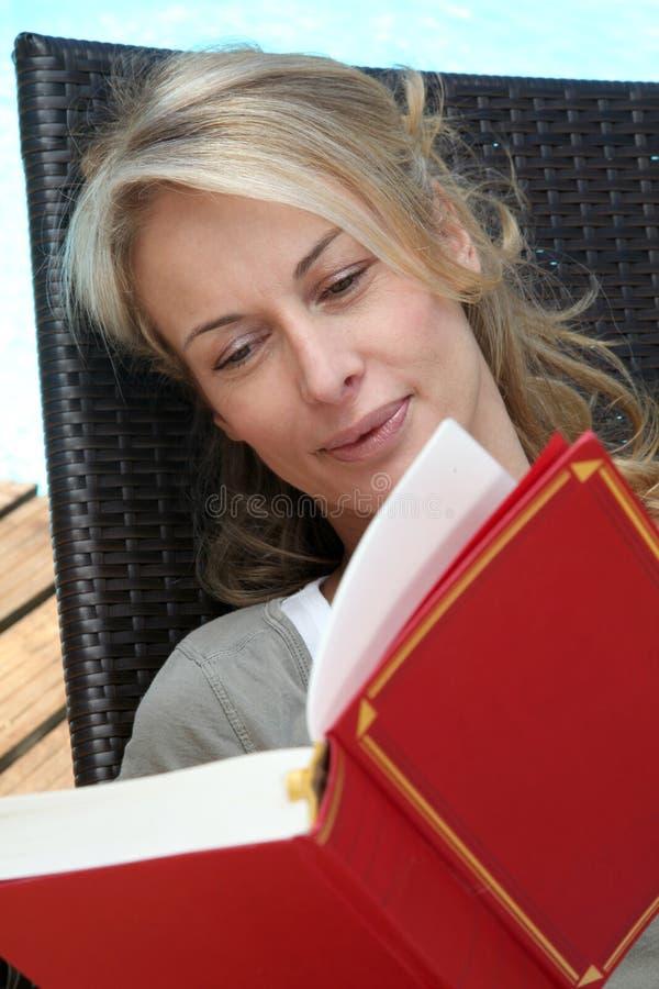 Kvinnaläsebok på terrass av simbassängen royaltyfria bilder