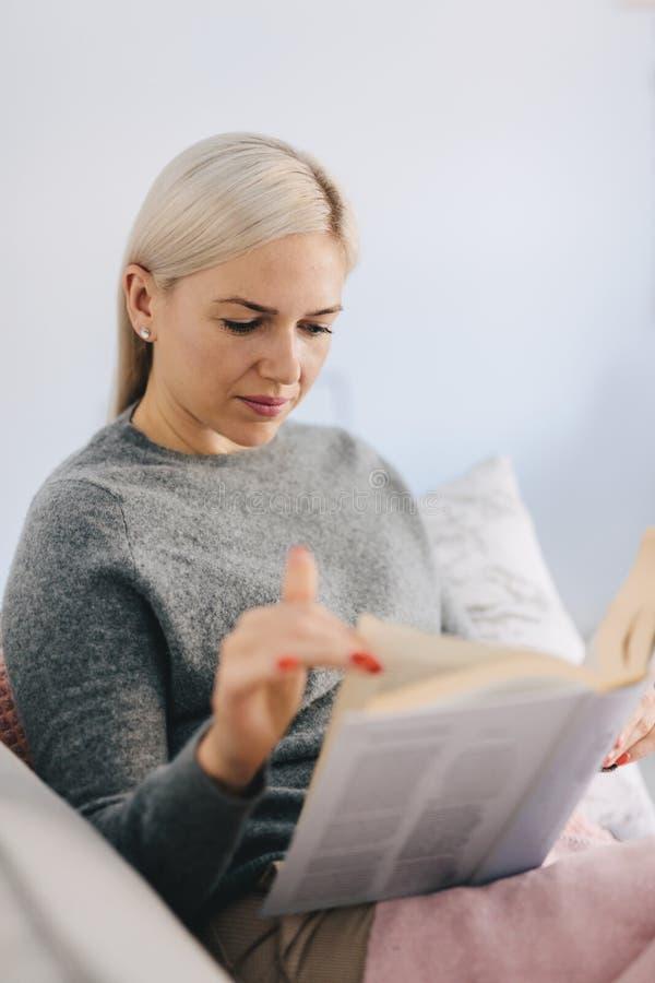 Kvinnaläsebok som sitter på soffan arkivbilder