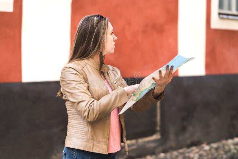 Kvinnaläsningöversikt och planläggningsrutt till destinationen arkivbilder