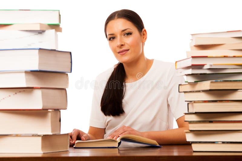 Kvinnaläsning bak tabellen mellan hög två av böcker arkivbilder