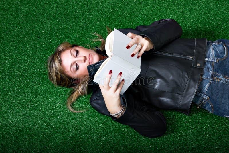 Kvinnaläsning bokar på gräs royaltyfri foto