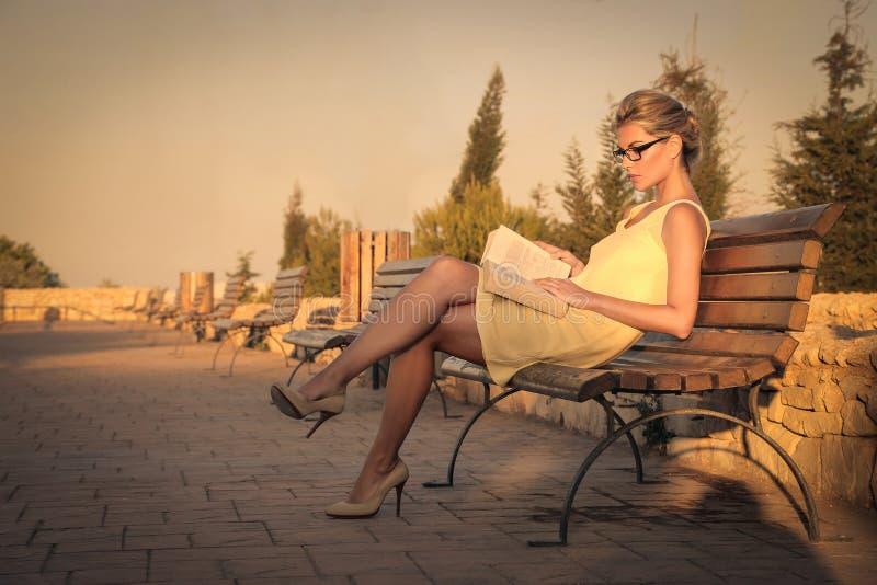Kvinnaläsning en boka arkivbild