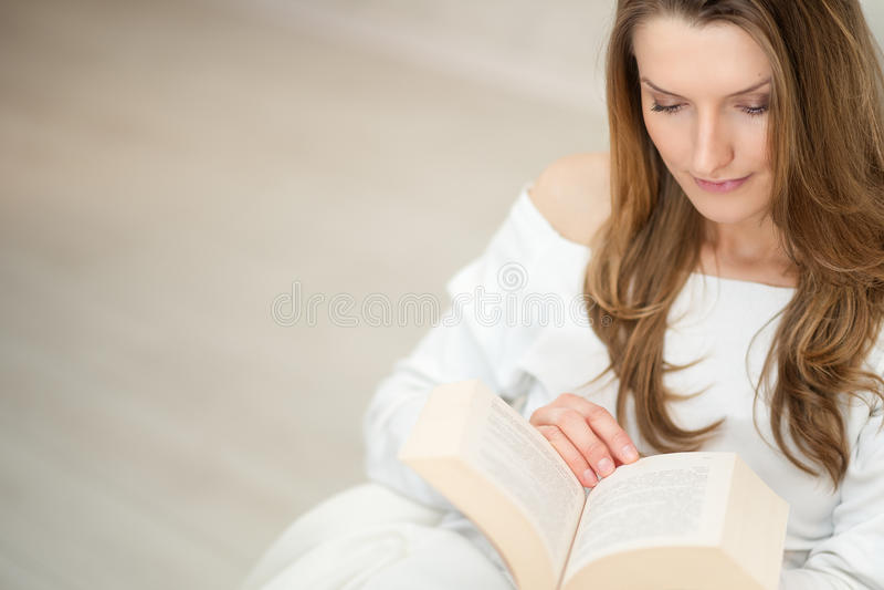 Kvinnaläsning en boka och koppla av på sofaen arkivfoton