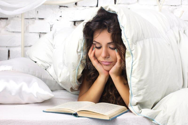 Kvinnaläsning i sängen royaltyfri bild