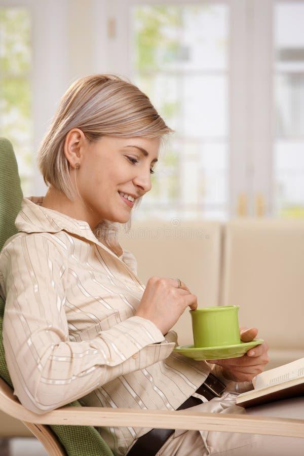 Kvinnaläsning med hemmastatt kaffe royaltyfri bild