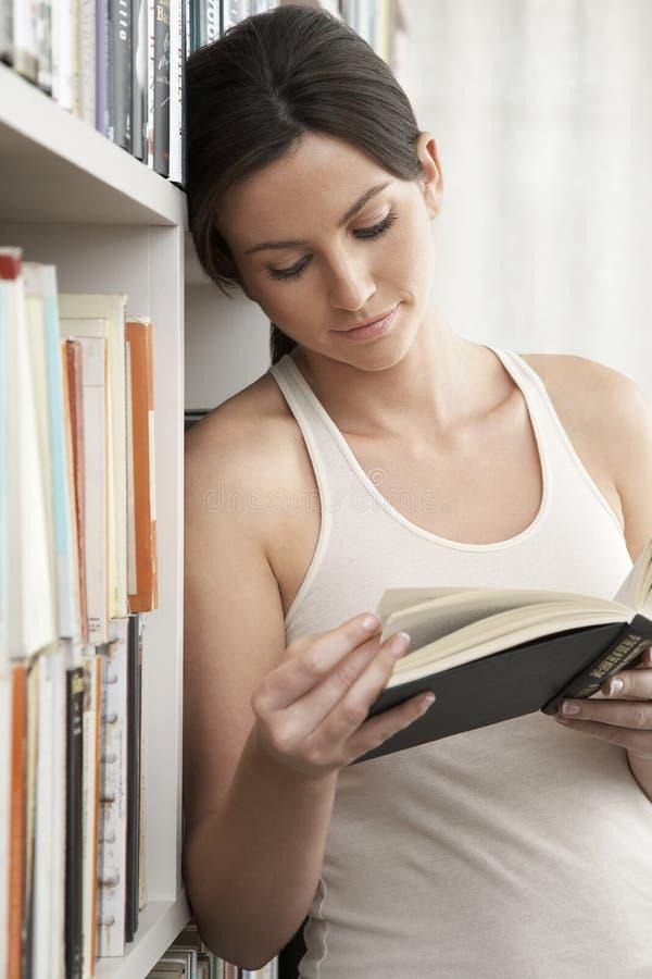 Kvinnaläsning, medan luta på bokhyllor royaltyfri bild