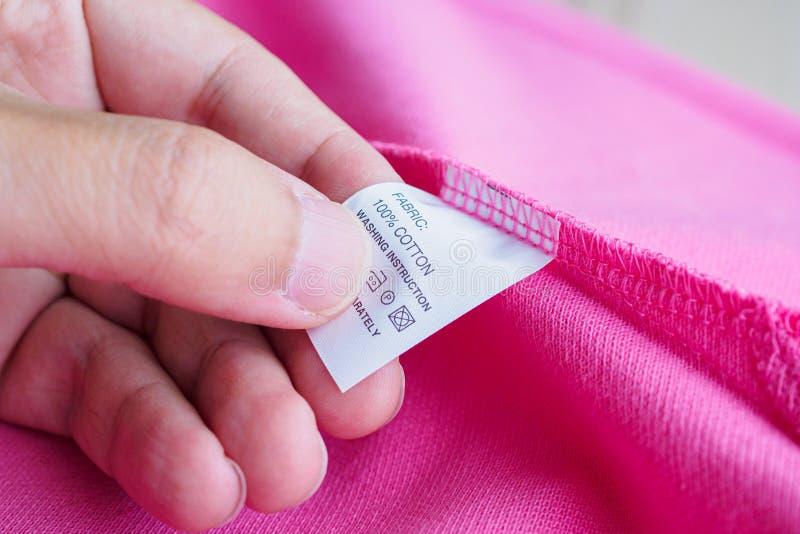 Kvinnaläsning på kläder för anvisningar för tvätteriomsorg tvättande märker på den rosa bomullsskjortan royaltyfria bilder