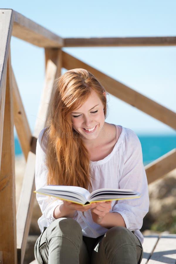Kvinnaläsning på sjösidan royaltyfri foto