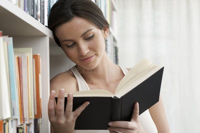 Kvinnaläsning vid bokhyllor hemma arkivbilder